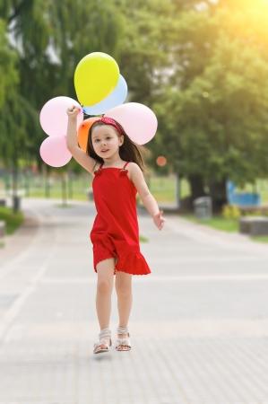 Gelukkig meisje met ballonnen lopen op het park