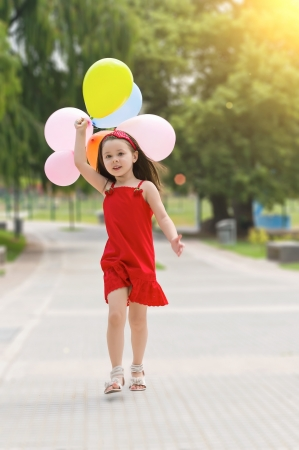 Muchacha feliz con los globos caminando en el parque