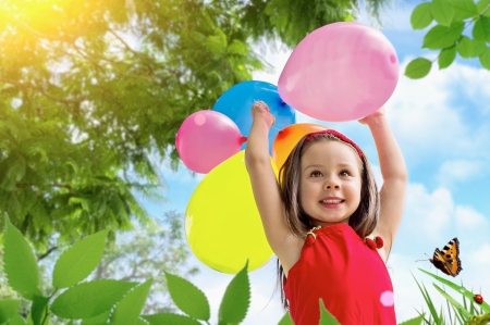 beautiful little girl playing with balloons photo