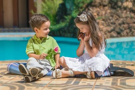 De kleine jongen geeft aan het meisje een bloem