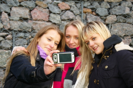 Group Of three Teenage Girls Taking Picture With Camera  photo