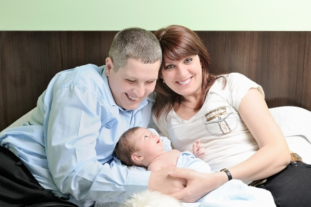 Couple with newborn baby at home photo