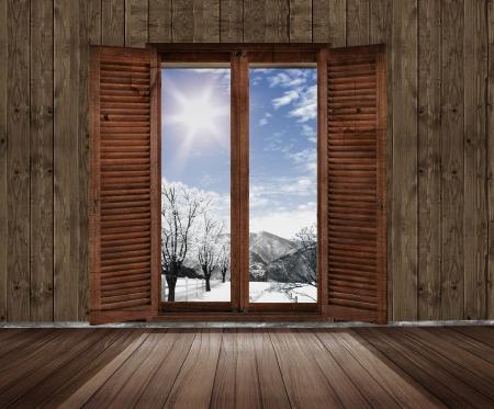 houten kamer met een raam met uitzicht op de tuin in de winter