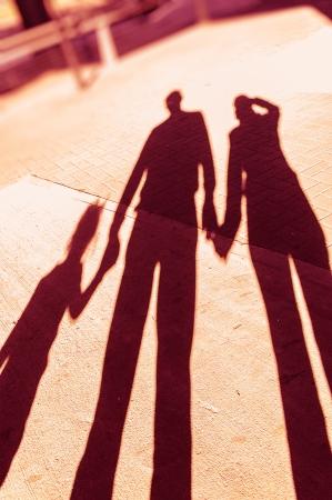 Schaduwen van een familie in het park hand in hand