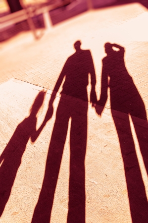 Shadows of a family in the park holding hands photo