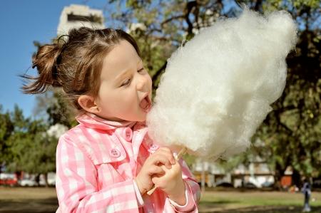 Hermosa niña comiendo candy-floss en el parque