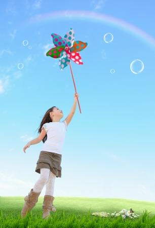 molino: Muchacha linda con el juguete molino de viento de color