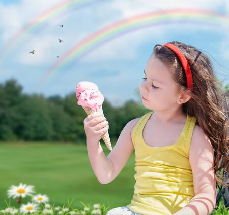 small beautiful girl eats ice cream outdoors
