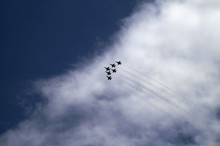 Six F-18 fighter jets flying in formation on a cloudy background