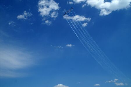 Five military jets flying up into the sky during air show
