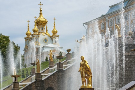 peterhof: Famous golden fountains in Peterhof near Saint Petersburg with baroque ornate church on background