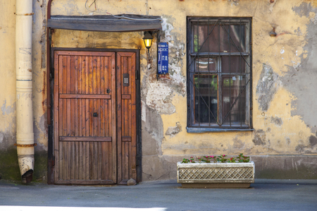 Grungy front door of common residential house in Russian big city suburb Stock Photo