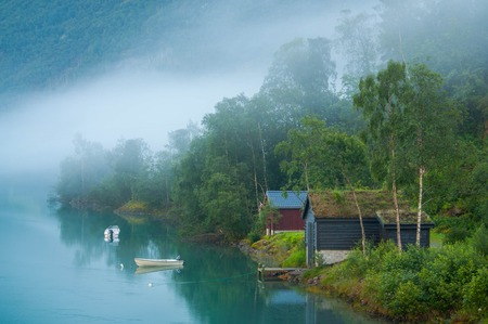 Sunrize sur un lac brumeux en Norvège. Vieilles maisons et bateaux