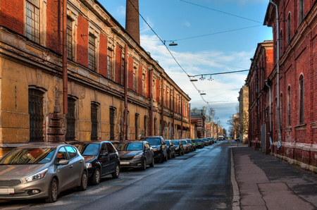 Old grunge street in Russian town with parked cars Stock Photo