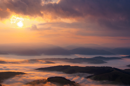 Misty sunrise in Carpathian mountains, clouds and fog in the dusk Stock fotó