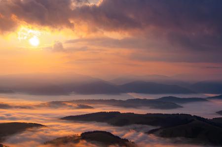 Nebliger Sonnenaufgang in den Karpaten, Wolken und Nebel in der Dämmerung Standard-Bild
