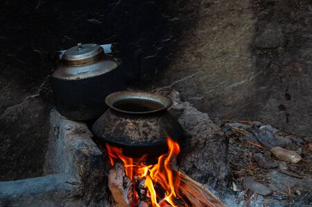 Traditional asian way to cook, old pot and kettle in fireplace