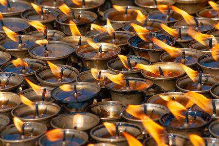Many oil candles burning at temple interior