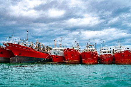 Many red vessels moored in the port of Puerto Deseado, Argentina Imagens