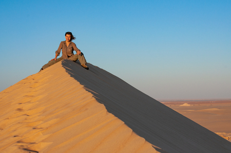Young woman in khaki clothes sitting on a huge sand dune in Sahara desert