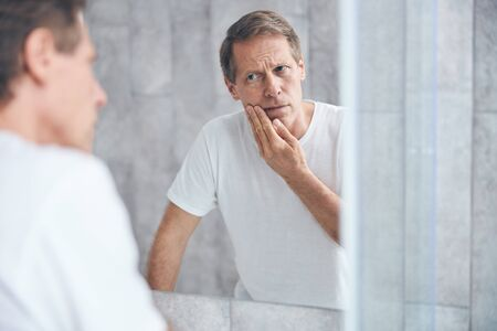 Sad man staring at his own reflection