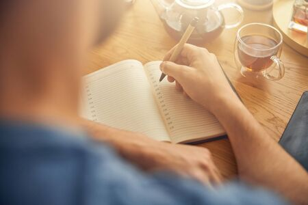 Male writing notes while sitting with drink