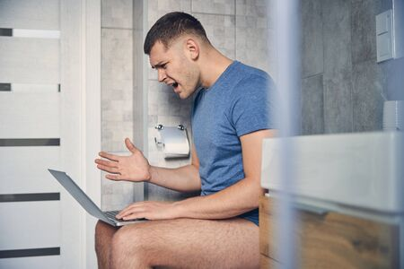 Young brunette male on a toilet with laptop