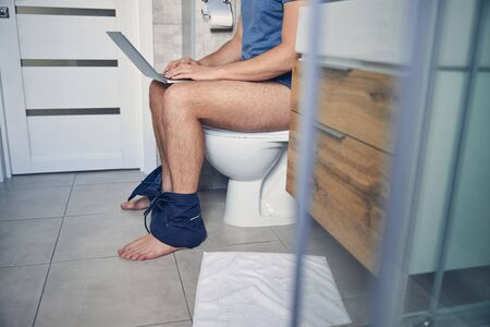 Man with laptop sitting on a toilet