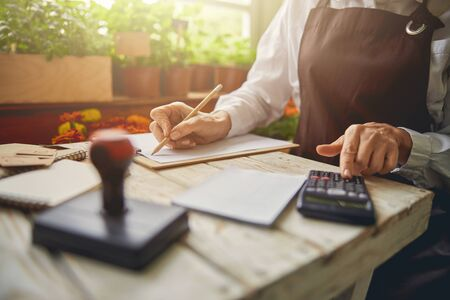 Caucasian middle-aged woman using a pocket calculator
