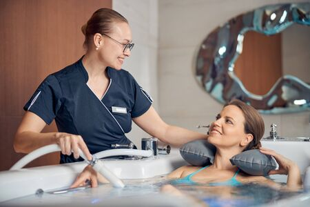 Contented lady receiving an underwater shower massage