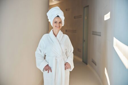 Female standing with her hands in the bathrobe pockets