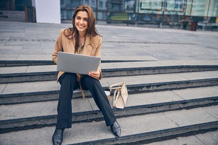 Good-looking female entrepreneur sitting on the stairs Archivio Fotografico