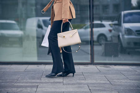 Young female in trendy pants strolling outdoors