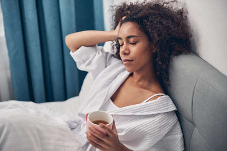 Calm woman lying in bed with her eyes shut