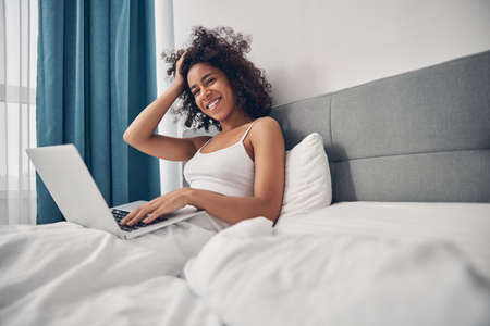 Contented young woman telecommuter sitting in bed Reklamní fotografie