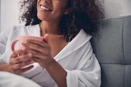 Woman in a bathrobe sitting in bed