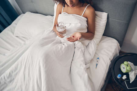 Dark-haired woman with a glass of water sitting in bed Reklamní fotografie