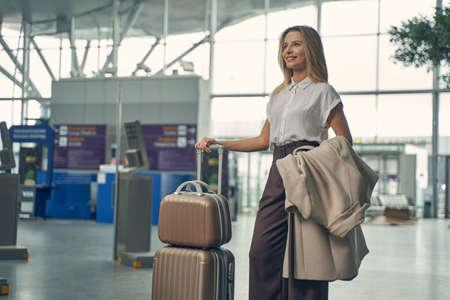 Cheerful female person standing near her suitcase Standard-Bild