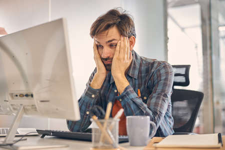Exhausted male worker using computer in office