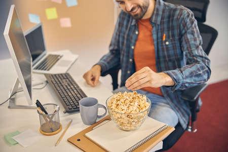 Cheerful young man eating popcorn at work