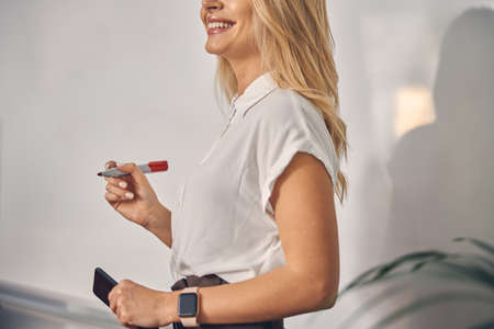 Cheerful young woman standing against whiteboard in office