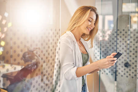 Beautiful young woman using cellphone at work