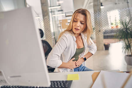 Unhappy female worker suffering from stomachache in office