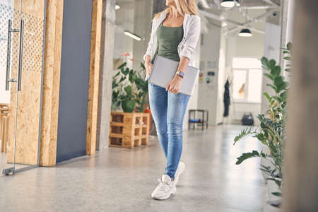 Young woman with laptop standing in office corridor
