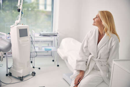 Cheerful longhaired woman looking at medical equipment