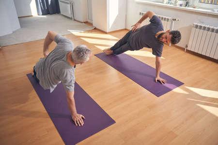 Two Caucasian men doing a yoga exercise Standard-Bild
