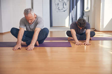 Modern yogis doing a stretching exercise indoors