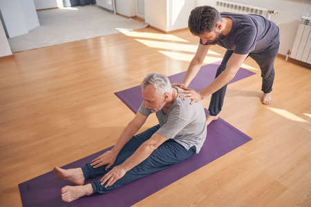 Mature man doing a stretching exercise on the mat Stock Photo