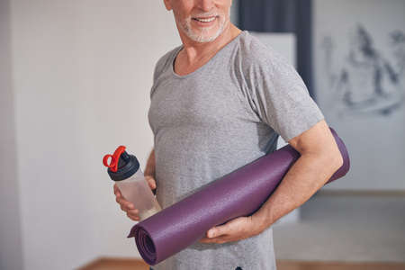 Man with a sports bottle and a yoga mat