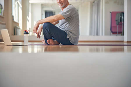 Barefoot man in sweatpants on the yoga mat